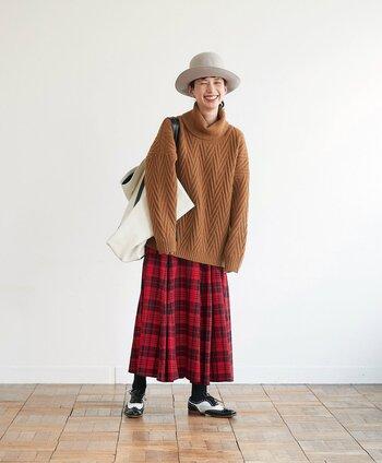 ブラウンカラーのタートルネックニットに、赤のチェック柄スカートを合わせたコーディネート。グレーのハットや大きめの白トートバッグが、カジュアル×フェミニンな雰囲気を演出しています。足元は白黒のシューズで、柄スカートのじゃまにならないスタイリングに。