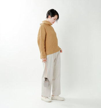 薄いキャメルカラーのタートルネックニットに、白のワイドパンツを合わせたナチュラルな印象のコーディネートです。足元は白のスニーカーで、ボトムスと色味を揃えて統一感をプラス。小さめの巾着バッグが、ベーシックな組み合わせのほどよいアクセントになっていますね♪
