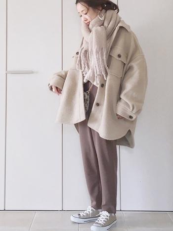 ぐるっとマフラーをひと巻きしたあとに、前に垂らしてサイドでふんわりと結んだコーディネートです。おしゃれに見せつつ首元にぐるぐるとマフラーを巻いて、しっかりと防寒も叶うスタイリング。マフラーと色を合わせたベージュ系コートに、ブラウン系のパンツでフェミニン×カジュアルな着こなしです。