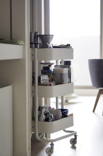 キッチンワゴンの段ごとに用途を変えて収納しているアイデア。 段ごとに目的が異なるアイテムを置けば、どこに何があるのかわかりやすく、在庫量もカテゴリ別に大まかに把握できるので便利です。  1段目には、コーヒーツールやコースターなどのティーセットを置いています。扉の開け閉めが必要なく、ワンアクションで取り出せるのでとっても便利なのだそう。