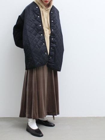 光沢によってグレーにもカーキにも見えるベロア素材のフレアスカート。キルティングコートの下でするんと揺れる上品な質感は、冬の装いにアクセントを与えてくれます。