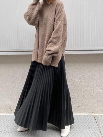重たくシックな黒スカートですが、プリーツのひだでニュアンスが加わります。淡いブラウンの優しいニット、足元にはホワイトのショートブーツを合わせることでクールな印象を和らげています。