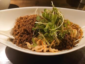 こちらはおすすめの、黒つゆなし担々麺。お店の自慢、9種類の生薬と香辛料の旨味が溢れる辣油と花椒を使用しています。混ぜれば混ぜるほど、コク深くクセになる一品。
