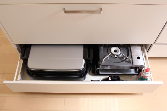 使う頻度の低い卓上コンロは、引き出し収納へ。鍋の季節以外はあまり登場しない家電なので、引き出しにしまえばすっきり。 こちらのお宅では、キッチンの引き出し収納の最下段に。