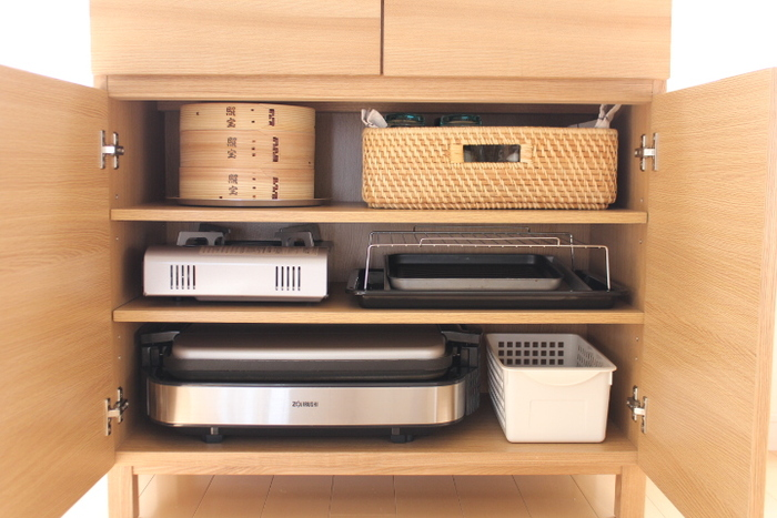 キッチンにこだわらずダイニングもキッチン家電の収納場所に。こちらのお宅では、扉付きキャビネットに調理家電をまとめています。空間をモノに合わせてきっちりと棚板で分けると、大きめの家電も無駄なく収納することができます。