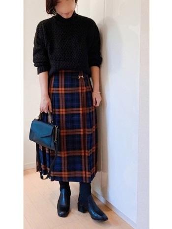 ちょっぴりレトロな雰囲気のビット付きプリーツスカート。黒でまとめたコーディネートは温かみのあるオレンジチェックがとても良く活きていますね。