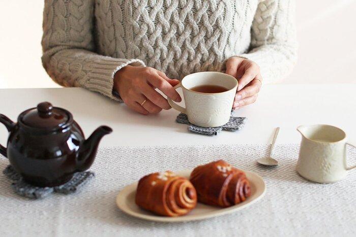 毛糸で編まれたクロス型のコースターにマグカップをのせて。まるでカップが毛糸のクッションに座っているような、ほっこりとした冬ならではの気分になれそう♪ 温かなドリンクがよりいっそうポカポカにしてくれるはずです。