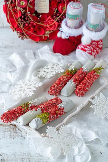 スティック型のフィナンシェにホワイトチョコをかけて、ストロベリーピースやピスタチオでクリスマスカラーにアレンジ。トッピングはチョコが固まらないうちにかけ、ラップの上からぎゅっと押さえて貼り付けるのがきれいに仕上げるためのコツです。