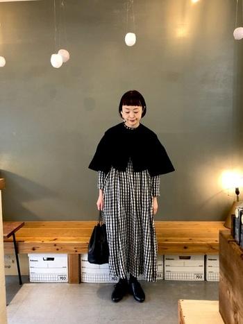 一枚で着るとガーリーなギンガムチェックワンピースを、シックに仕上げた大人の着こなし。モダンな黒ボレロやレザー小物を合わせれば、洗練されたナチュラルコーデが完成します。