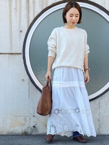 白ニットにコットンの刺繍スカートを合わせて。大人に着こなすコツは、デニムをレイヤードしたり、パールをたすき掛けにしてちらりとアクセントを作っているところ。