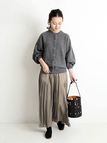 細いプリーツが施されたさらりとしたスカートには、ぽわんとした袖コンシャスなカーデを合わせて温かみをプラス。コーデをぼやけさせないために、足元とバッグは黒で統一。