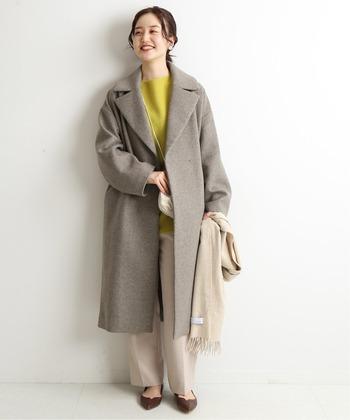 モノトーン系のコートでも、ライトグレーなら重すぎず軽やかな印象に。明るめのからし色ニットと合わせれば、顔色もパッと柔らぐ華やかさを纏うことができます。