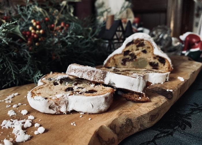 最近は日本でも見かけることが多くなったシュトレン。ドイツ語で「坑道」という意味で、細長い形からそう呼ばれるようになったようです。また表面に粉砂糖が隙間なく振りかけられた姿が、幼いキリストを産着でくるんだように見えると考えられ、クリスマスでは定番のお菓子となっています。日持ちがするので、アドヴェントの期間から一切れずつ食べ進めていくと、たくさん混ぜ込まれたレーズンやオレンジピールの味わいが生地に移って、味の違いを楽しむことができます。