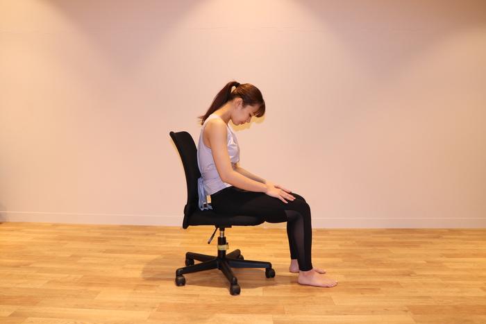 ① 基本の姿勢のまま息を吸って・・・息を吐きながら背中を丸め、目線をおへそに向ける。