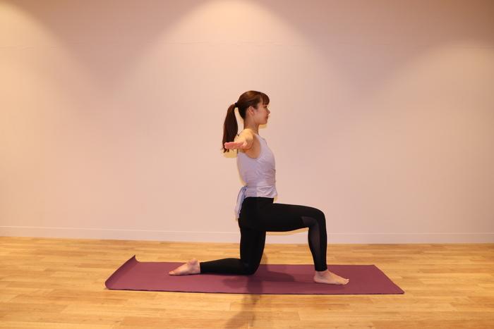① 右足を前につき、左足は膝を90度に曲げ、つま先を寝かせる。両膝とも角度は90度です。  息を吸いながら、両手を横から肩の高さまで上げる。