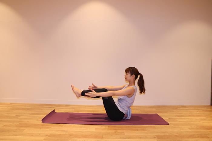 ① 片方ずつ脚を上げて前に伸ばす。下半身が安定したら、膝下は床と平行に保ったまま、両手は前に伸ばします。手の平は内側に向けましょう。そして、そのまま息を吸います。