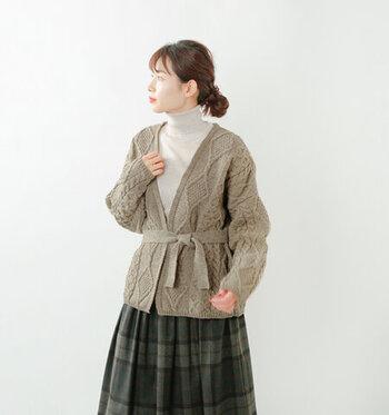ケーブル編みのニットカーディガンは、留め具がない仕様でフロントをリボンで結ぶタイプ。ウエストマークにも使えるので、スタイルアップ効果にも期待ができる一着です。ゆるっと羽織ったり、きっちり前を結んだりと、一枚でさまざまなコーディネートが楽しめます。