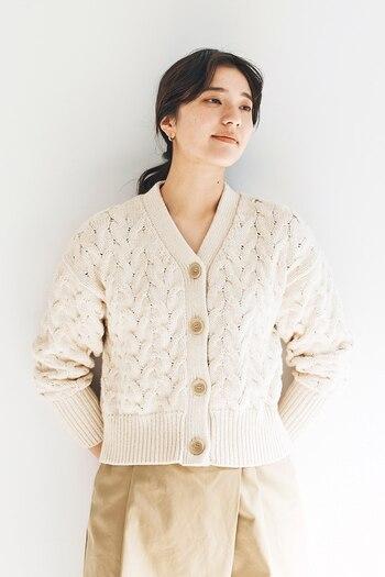 ケーブル編みの白ニットカーディガンは、程よく短めの丈感でトップスのように着こなせるアイテムです。前のボタンをすべて留めれば、タックインをしなくてもバランスのよいコーディネートが完成。パンツにもスカートにも合わせやすい一枚です。