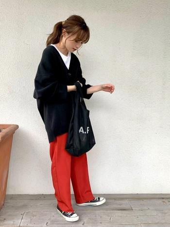 黒のカーディガンに白インナーを合わせて、ボトムスに赤のワイドパンツをチョイスしたスタイリングです。黒のスニーカーやトートバッグで、赤パンツをカジュアルに着こなしています。シンプルなアイテムの組み合わせも、色使いでおしゃれ度がグッと高まりますね♪