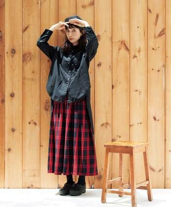 赤のタータンチェック柄スカートに、黒シャツを合わせたコーディネート。スカート以外はすべて黒で揃えて、全体的にシックな印象のスカートコーデに仕上げています。