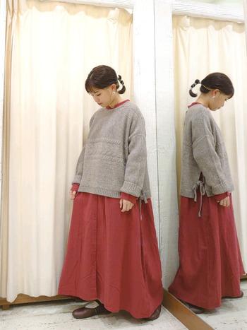 ゆったりシルエットの赤ワンピースに、グレーのニットトップスをレイヤードしたコーディネートです。襟や袖からもワンピースをチラ見せして、バランスのよい重ね着コーデに仕上げています。