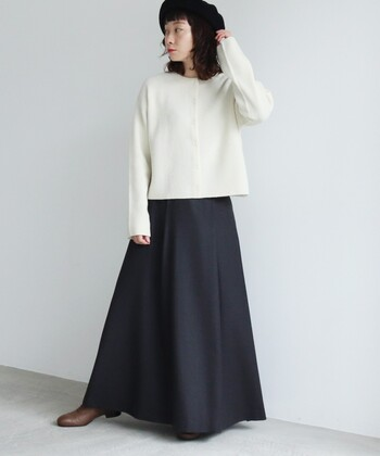 カシミヤ素材の白カーディガンに、ネイビーのロングスカートを合わせたコーディネートです。足元はブラウンのブーツで、シックな雰囲気にまとめています。ベレー帽を頭にかぶって、シンプルコーデに女性らしさと季節感をプラス。