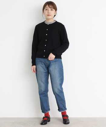 黒のカーディガンのボタンをすべて留め、襟元からフリルインナーをちらりと覗かせたコーディネートです。ボトムスはデニムでベーシックな印象ですが、足元はストラップシューズと赤靴下で、ワンアクセントをプラスしています。