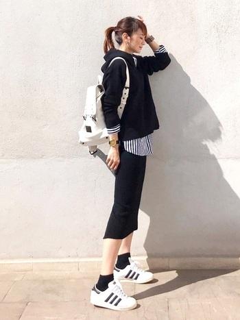 黒パーカー×タイトスカートの同じカラーの組み合わせですが、インナーからストライプシャツを覗かせることでアクセントを。足元のスニーカーやリュック使いでアクティブなコーデに仕上がっています。