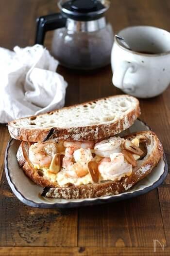 ガーリックオイルでプリッと焼き上げたエビをクリーミーな卵サラダと一緒にパンに挟んだ、贅沢なサンドイッチ。食パンやバゲットなど、お好みのパンで作ってみてくださいね!
