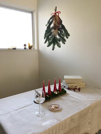 テーブルの中央にキャンドルとオーナメントを飾って。赤いキャンドルがサンタ帽のようでとってもキュートですね。スワッグを吊るすのもおしゃれなアイデアです!