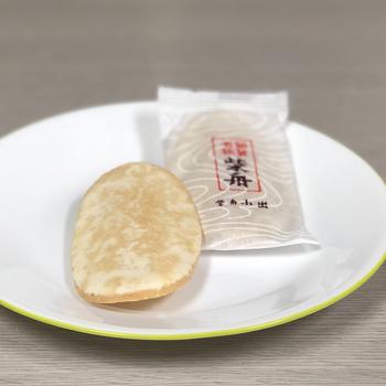 【柴舟小出】の「柴舟」は生姜の辛みと砂糖の甘さが絶妙なおせんべい。舟のように反った形と白砂糖で薄化粧した姿が上品です。