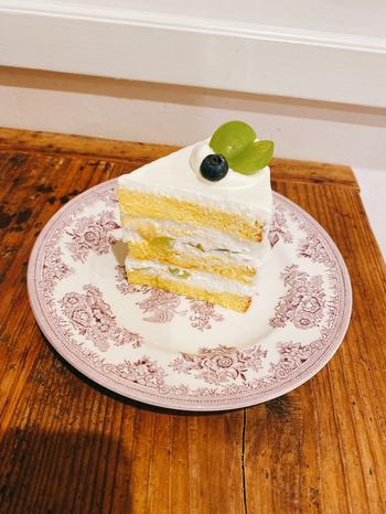 きめ細かいスポンジとなめらかなクリームが評判のショートケーキ。旬のフルーツがサンドされていて、こちらはシャインマスカットです。美しいプレートに盛り付けられていて、リッチな気分を味わえますよ。