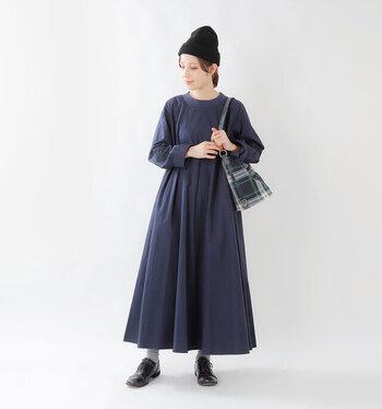 黒のニット帽に、ネイビーのワンピースを合わせたコーディネートです。足元もグレーの靴下に黒のフラットシューズを合わせて、全体をダークトーンでまとめています。落ち着いたカラーリングながらも、チェック柄のバッグをプラスして、ほどよいアクセントに。