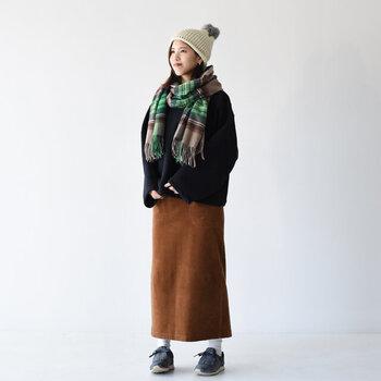 白のニット帽に、黒アウターとブラウンのタイトスカートを合わせたコーディネートです。無地のアイテムを組み合わせているので、チェック柄のストールが程よいアクセントになっています。足元はスニーカーで、カジュアル感を強めた大人女子コーデに。