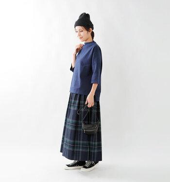 黒のニット帽に、ネイビーのトップスとチェック柄スカートを合わせたコーディネートです。全体的にダークトーンなアイテムをチョイスして、色味に統一感を与えているのがポイント。小物は黒で揃えて、ぼんやりとしすぎないよう引き締め感もプラスしています。