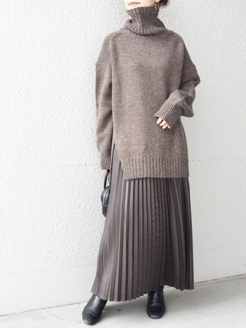 季節にもしっくりくるブラウンのコーデ。裾のスリットによってスタイルアップできるニットに、フェイクレザーのスカートを合わせて異素材感を楽しみましょう。