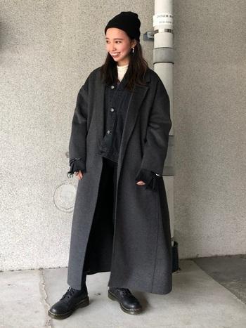 黒のニット帽に、ダークグレーのロングコートを合わせたコーディネート。インナーの白をチラ見せしている以外は、全体をダークトーンでまとめたメンズライクなスタイリングです。カジュアルなイメージの強いニット帽を、クールに着こなしています。