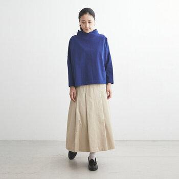 ブルーのタートルネックトップスに、薄いベージュのスカートを合わせた着こなし。ちょっぴり短め丈のトップスを選べば、あえてボトムスにインしなくても全身のバランスがとれたコーディネートが完成します。黒シューズ×白靴下で、印象的なブルーのトップスを柔らかな印象にまとめています。