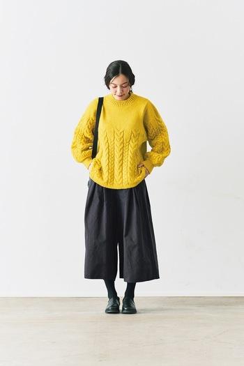 フロントの下側のみに、アラン柄のケーブル編みを施したイエローのニットに、黒のワイドパンツを合わせたスタイリング。パンツは七分丈なので、厚手のレギンスやタイツを着込んでも足首を見せることで着ぶくれしないあったかコーデに仕上がります。