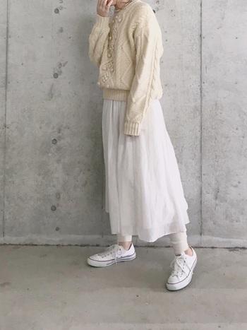 厚手のケーブルニット×ふんわりフレアスカートで、ボリューム感を楽しむホワイトコーデ。ローカットスニーカーでさりげなく足首を見せているのが、もたつかないポイントです。