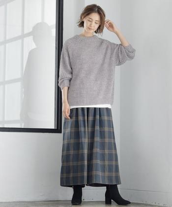 グレーのニットトップスに、チェック柄のワイドパンツを合わせたコーディネートです。スカート見えするワイドパンツなら、インナーの重ね着も楽ちん。二の腕周りがゆったりしているニットトップスを選べば、長袖のインナーも重ねやすいです。