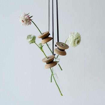置くタイプではなく、吊るすタイプのフラワーベース。壁のフックに掛けたり、カーテンレールに吊るすなどして楽しめるデザインです。2mの紐を、好みのバランスでカットしてもOK。木製パーツとガラスの組み合わせが、ナチュラルながらも繊細なアイテムです。