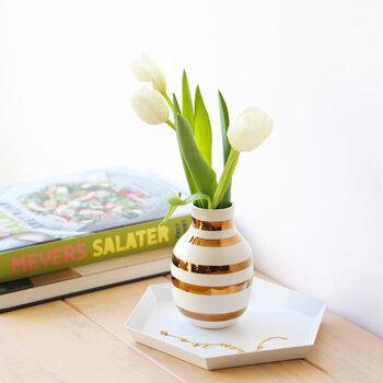 デンマークで1839年に創業した、老舗陶磁器メーカーの「KAHLER(ケーラー)」。そんなケーラーの生誕175周年を記念して作られた、フラワーベースです。職人による手書きのボーダー柄が、スタイリッシュな印象を与えます。白とゴールドの組み合わせは、季節を問わずに愛用したくなるデザインです。