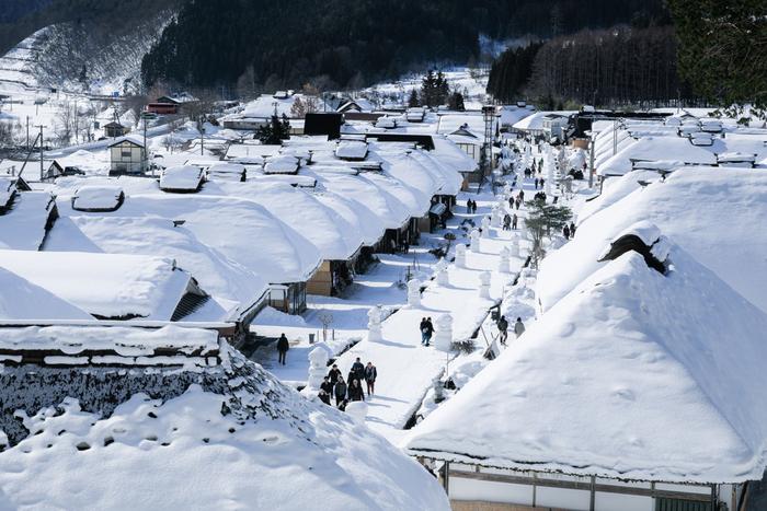 福島県南会津郡下郷町にある大内宿は、江戸時代における会津西街道の宿場町です。茅葺屋根の民家が街道沿いに立ち並んでいる大内宿は、国の重要伝統的建造物群保存地区にも指定されています。およそ500メートルにわたって、すっぽりと雪に包まれた茅葺屋根の民家が整備されている街道を歩いていると、まるで日本昔話の世界に入り込んだかのような気分を味わうことができます。