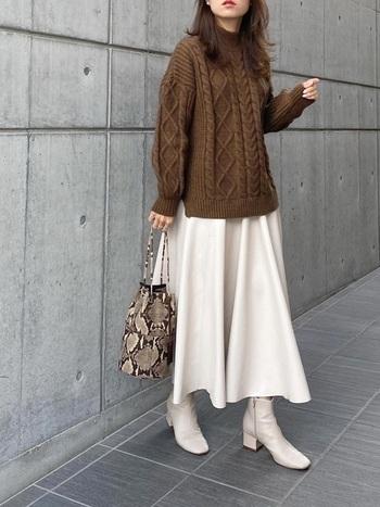 ホワイトのレザーアイテムならスカートだけでなく、ブーツやバッグにもたくさん取り入れても女性らしいコーデに。ブラウンのケーブルニットがより柔らかな雰囲気をつくってくれています。