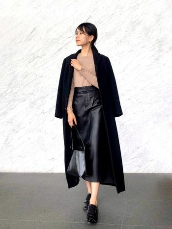 ブラックとベージュで少しフォーマルな雰囲気が漂う大人な着こなし。レザーの高級感を活かし、タイトスカートをロング丈のアウターでスタイリッシュにまとめています。