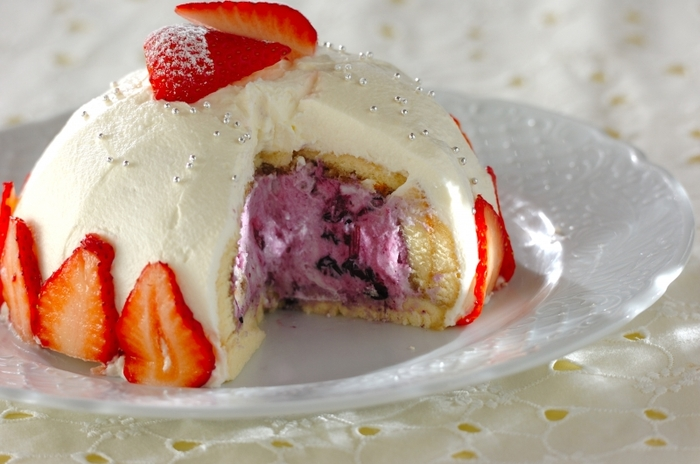 生クリームの白と、ブルーベリーソースの紫のコントラストが美しいケーキ。ボウルに沿ってスポンジを敷き詰めれば、綺麗なドーム型に仕上がります。イチゴを飾ると華やかさアップ♪