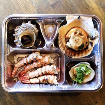 魚介好きの方必見!「蛸焼き・炉ばた 満家」では、新鮮な魚介をふんだんに使ったテイクアウトを提供しています。例えば「浜焼きセット」では、ホタテやハマグリをリーズナブルなお値段でお届け。スルメイカやホッケ、カマ塩焼きなどの炉端焼きのほか、いろいろな味が楽しめる自慢の蛸焼き、お酒にも合うメニューを取り揃えた「飲みセット」も注文することができます。居酒屋メニューを外で食べられるのが嬉しいですね。