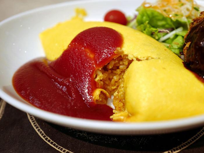 「たいめいけん・デリカ」は新宿駅新南口から徒歩3分、新宿タカシマヤの地下1階にあるイートインスペースを備えたお店。日本橋にある老舗洋食屋「たいめいけん」のデリカショップです。  均一な美しい黄色のふっくらと仕上げられた薄めの卵で丁寧に包まれたライスにはハムと玉ねぎが入っています。王道ともいえるオムライスは、なめらかな卵の食感が秀逸。