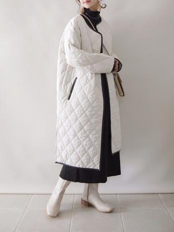 カジュアルな印象のキルティングコートをより女性らしくエレガントに着こなしたい方にオススメのコーデ。コートはロング丈の白、足元は白ブーツ、トップス、スカートとパイピングは黒の、モノトーンスタイルが印象的です。